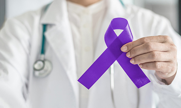 A clinician holds a purple cancer awareness ribbon