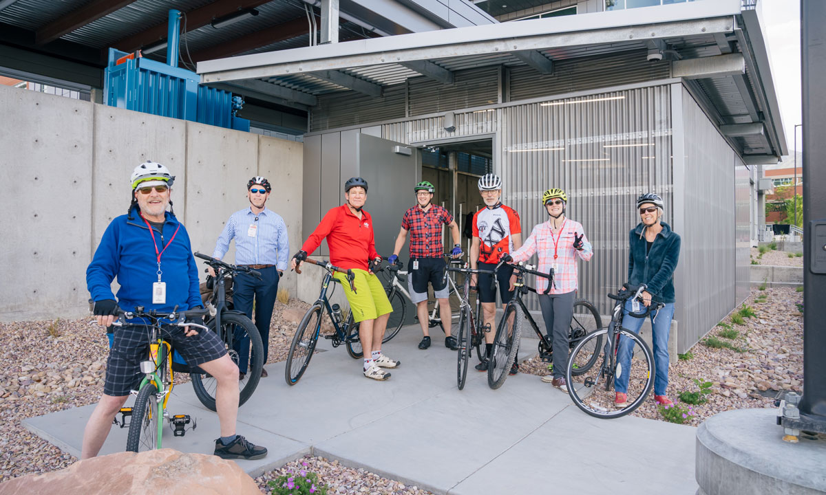 Seven employees pose with their bikes in front of the new bike storage facility.