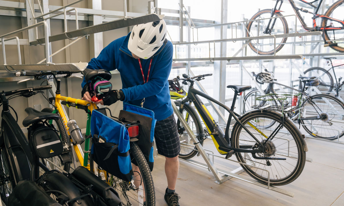 A person is locking is bike in the new bike storage facility. There are seven other bikes around him, one of which is on an upper rack.